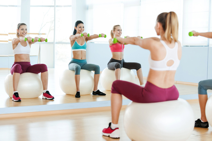 Women exercising with dumbbells. Three beautiful young women in